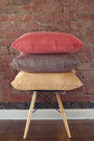 Stack of three linen cushions on chair brick wall background Royalty Free Stock Photos