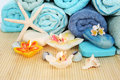 Stack of towels soaps candles stones flowers on mat background Stock Photography