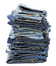 A stack of various pairs of jeans pants isolated on white background Stock Images