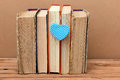 Stack of vintage books with heart shape old on wooden table Stock Photos