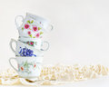 Stack of vintage tea cups antique stacked for high on a white background Royalty Free Stock Photos