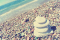 Stack of white stones balancing on the pebbly beach retro a sunny day image filtered in faded washed out style summer vintage Royalty Free Stock Image