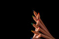 Stacked color pencils creatively of different colors on black Royalty Free Stock Photos