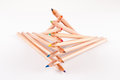 Stacked color pencils creatively of different colors on white Stock Photos