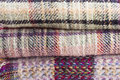 Stacked and folded picnic blankets with woven checked multicolored pattern Royalty Free Stock Image