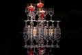 Stacked glassware stemmed in tiers on reflective black surface Stock Image
