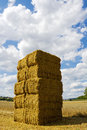 Stacked hay bales against blue summer sky with clouds Royalty Free Stock Photo