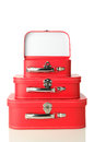 Stacked suitcases one open three red on a white background with slight reflection top bag is vertical format Royalty Free Stock Image