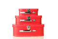 Stacked suitcases three red on a white background with slight reflection Stock Photos