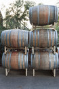 Stacked wine barrels stained with red on metal racks outside Stock Photo