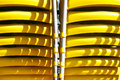 Stacked yellow chairs close up on two rows of plastic Stock Photo