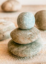 Stacked zen stones natural rounded weathered with scattered beach sand conceptual of a spa wellness spirituality and meditation Stock Photo