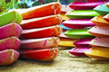 Stacking colorful canoes after the trip of the day Royalty Free Stock Image