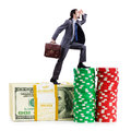 Stacks of chips and climbing businessman Royalty Free Stock Photo