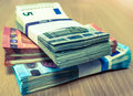 Stacks of Euro bills on a pine desk in fives, tens and twenties Royalty Free Stock Photo