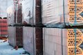 Stacks of silicate bricks on wooden pallets and in polyethylene Royalty Free Stock Photo
