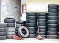Stacks of used car tires and hydraulic floor jack symbolize recycle business Royalty Free Stock Images