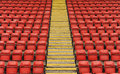 Stadium seats with steps red plastic in a sports a central yellow staircase Royalty Free Stock Images