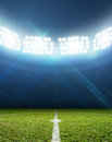 Stadium and soccer pitch a with a marked green grass at night under illuminated floodlights Royalty Free Stock Photo