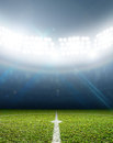 Stadium and soccer pitch a with a marked green grass at night under illuminated floodlights Royalty Free Stock Images