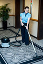 Staff cleaning carpet with a vacuum cleaner Royalty Free Stock Photo