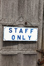 Staff only notice hanging on an old wooden door Stock Photography