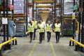 Staff in reflective vests walking to camera in a warehouse Royalty Free Stock Photo