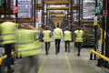 Staff in reflective vests walking in a warehouse, back view Royalty Free Stock Photo