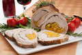 Staffed pork loin roulade dried apricots pistachios and rosemary served with salad tomatoes and glass of red wine Stock Images
