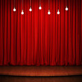 Stage with red curtain, wooden flooring and light bulbs