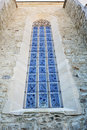 Stained glass window on old church wall stone masonry. Royalty Free Stock Photo