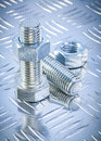 Stainless bolt details and threaded construction nuts on channel channeled metal background maintenance concept Royalty Free Stock Photos