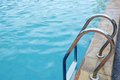 Stainless ladder in the pool with blue water Royalty Free Stock Images