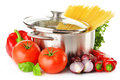 Stainless pot with spaghetti and variety of raw vegetables on white Stock Photo