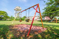 Stainless steel childrens swing set with partly cloudy blue sky Stock Image