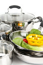 Stainless steel pots and pans with vegetables Royalty Free Stock Photography