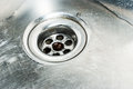 Stainless steel sink plug hole close up with water Stock Photos