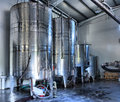 Stainless steel wine vats in a row inside the winery Stock Photos