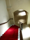 Stairs descending image of a red carpeted stairwell leading down towards an arched entrance Royalty Free Stock Image