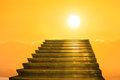 Stairway to heaven stairs towards sun on the orange sunset with clouds Royalty Free Stock Photography