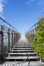 Stairway to heaven steel staircase going up to a blue sky with clouds concept of the road the road success modern Royalty Free Stock Photography
