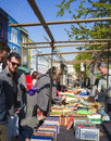 Stalls of portobello notting hill london england people gaze at old books on a beautiful day at the road market in the district Royalty Free Stock Photos