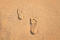 Stamp of feet on sand on the beach with sunshine Royalty Free Stock Photo