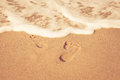 Stamp of feet on sand on the beach with sunshine in the morning Royalty Free Stock Photo