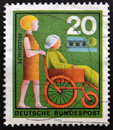 A stamp printed in  Germany shows woman Assisting Stock Image