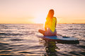 Stand up paddle boarding on a quiet sea with warm summer sunset colors. Relaxing on ocean Royalty Free Stock Photo