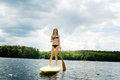 Stand up paddle boarding teen girl on a lake in haliburton ontario Royalty Free Stock Photos