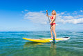 Stand up paddle surfing in hawaii attractive young woman beautiful tropical ocean active beach lifestyle Royalty Free Stock Photos