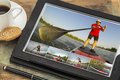 Stand up paddling on digital tablet reviewing pictures of featuring a senior male a computer in black leather case with coffee cup Royalty Free Stock Image