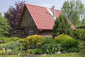 Standard wooden shed no name rural with red tile roof in the european decorative garden landscape sunny day Stock Photos